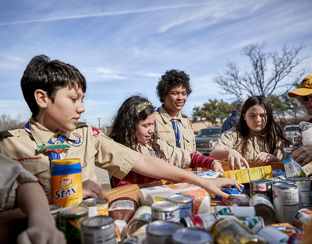 Scouts BSA sort donated food to serve their community
